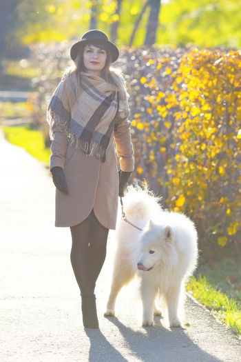 Portrait of woman on footpath with dog in park