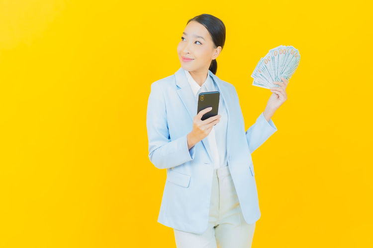 Young woman using mobile phone against yellow background
