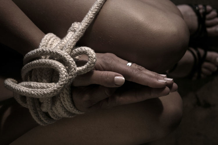 Midsection of woman tied with rope