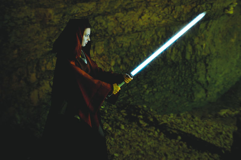 Side view of woman holding sword in cave
