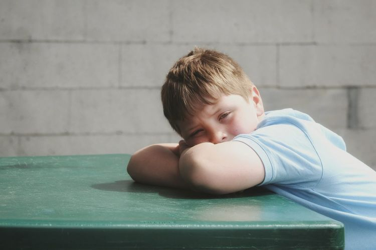 Portrait of boy lying down on table against wall