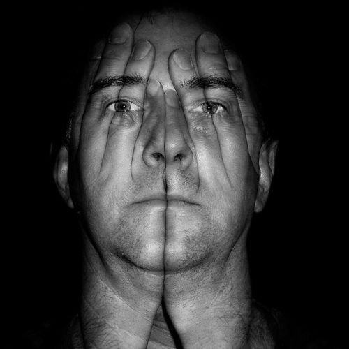 Digital Composite Image Of Hands On Man Face Against Black Background
