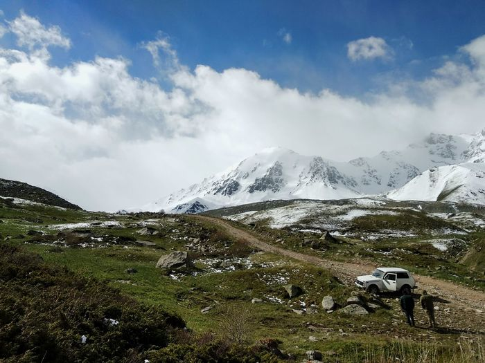 Scenic view of snowcapped mountains against sky with two people and vehicle