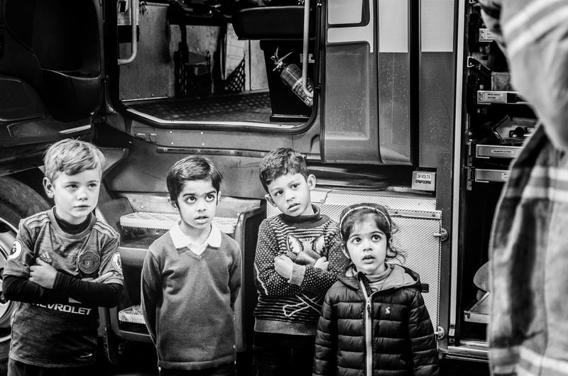 Four pairs of curious eyes look on with awe as the fireman puts on his outfit and shows them the fire engine's parts. 4 Kids Attention Awe Awestruck Bewildered Boys Childhood Children Curious Day Demonstration Education Fire Engine Fire Station Fire Truck Girls Indoors  Kids Being Attentive Novel Real People Safety Standing Starting Young Teaching Training Break The Mold