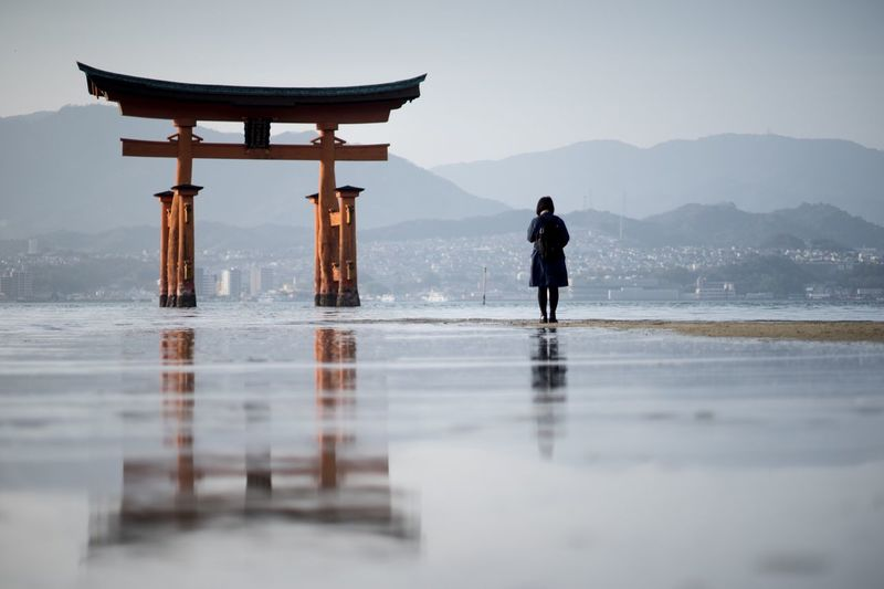 Rear View Of Woman Standing At Beach By Torii Gate Against Sky