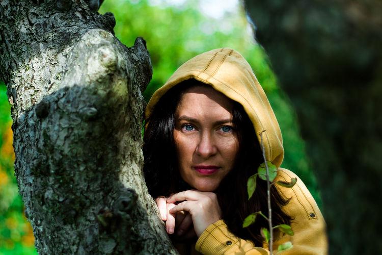 Portrait of woman holding tree trunk