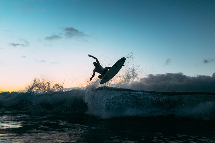 Silhouette man surfing in sea against sky at sunset