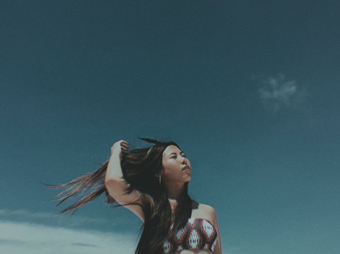 Low angle view of woman looking up against sky