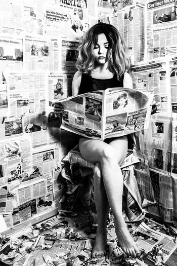 Young woman reading newspaper in room