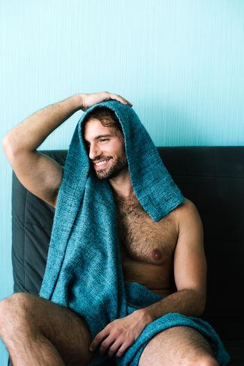 Smiling shirtless young man sitting on sofa at home