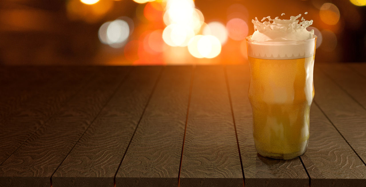 CLOSE-UP OF BEER GLASS ON TABLE AGAINST ILLUMINATED BACKGROUND