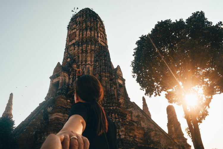 Cropped Image Of Man Holding Hands With Girlfriend Against Old Ruin During Sunset