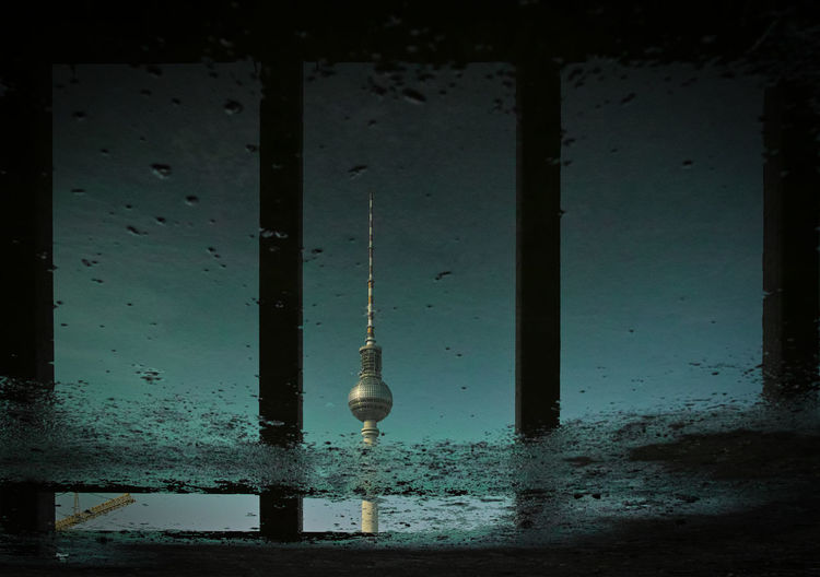 Upside Down Image Of Fernsehturm Reflection In Puddle
