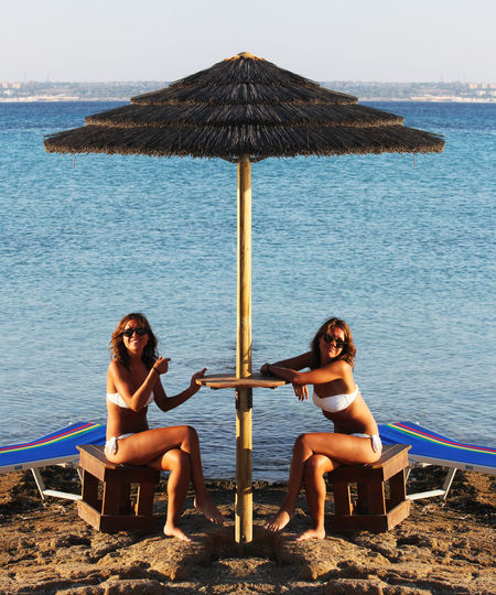 Twins Twin Adult Beach Friendship Full Length Land Leisure Activity Lifestyles Nature Outdoors Real People Relaxation Sea Sitting Togetherness Two People Water Women Young Adult Young Women