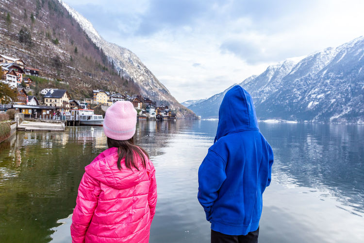 Back view of two young sisters looking at the hallstatt town across the lake with mountain ranges