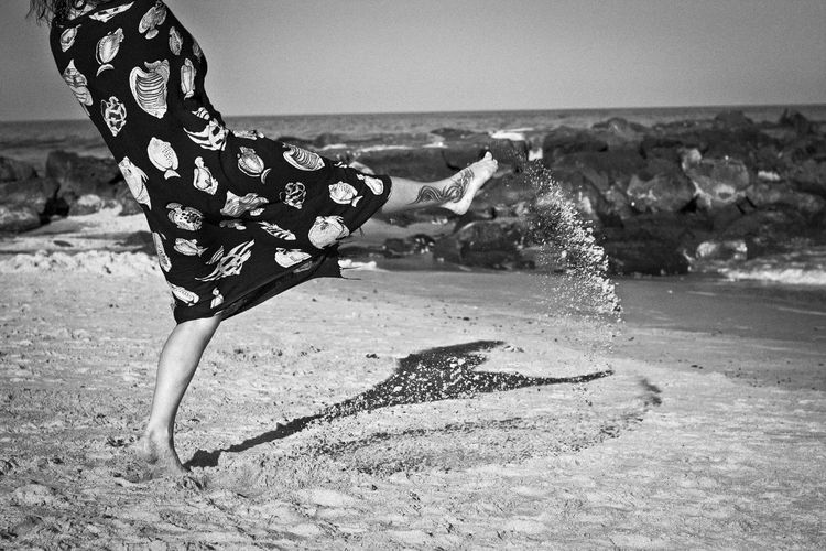 Low section of woman kicking sand at beach against sky