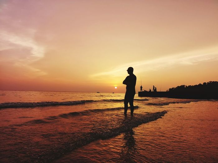 Silhouette Man Standing On Shore At Beach Against Sky During Sunset