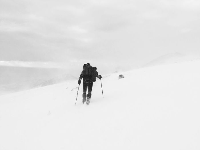 Rear view of person hiking on snowcapped mountain against sky