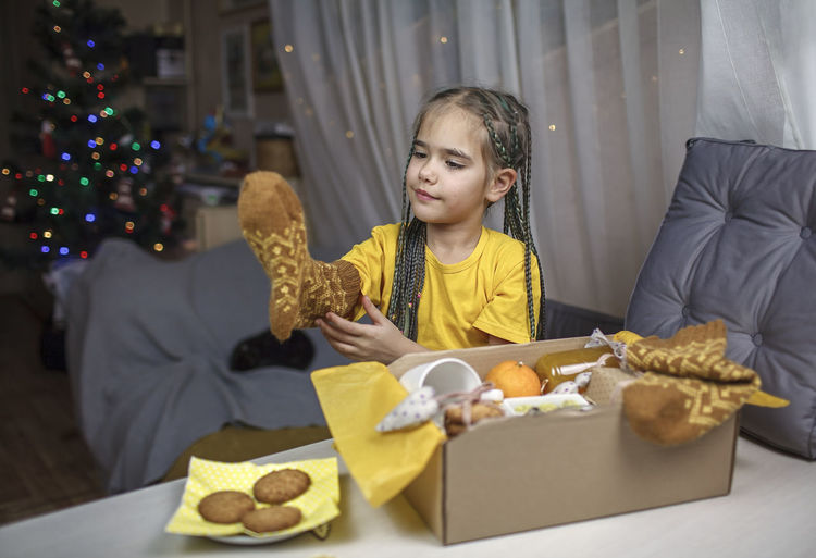 Girl packing care box with tea, honey, cookies and knitted wool socks for grandmother on christmas