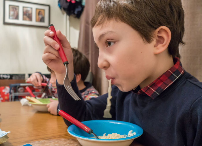Close-up of boy eating noodles while sitting at table