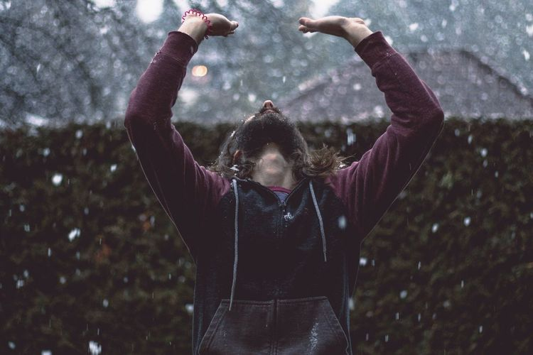 Man Standing Against Hedge During Snow Fall