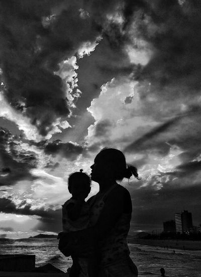 Silhouette of people against cloudy sky