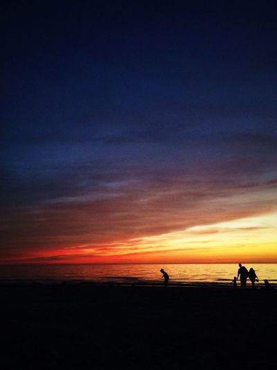 Silhouette family at beach against sky during sunset