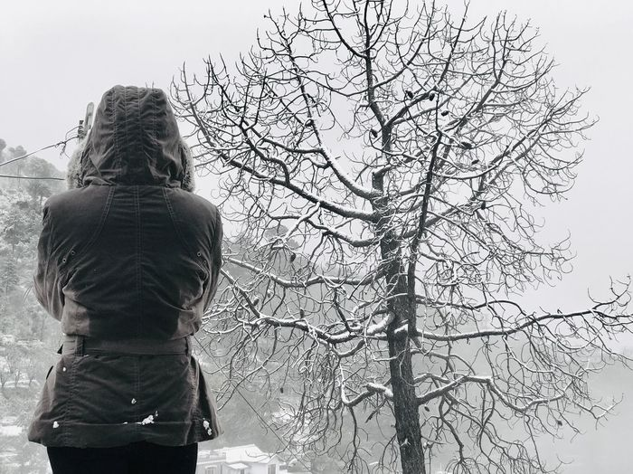 Rear view of woman standing by bare tree against sky