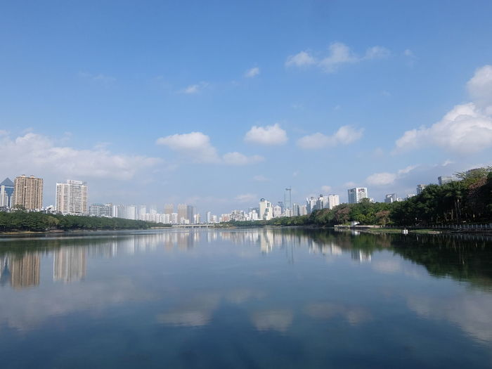 Scenic view of lake by buildings against sky