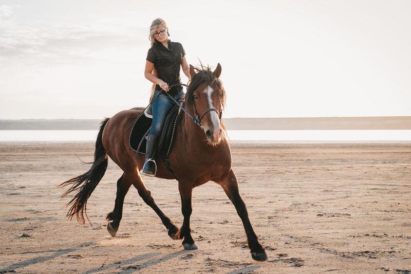 Full length of a man riding horse on beach