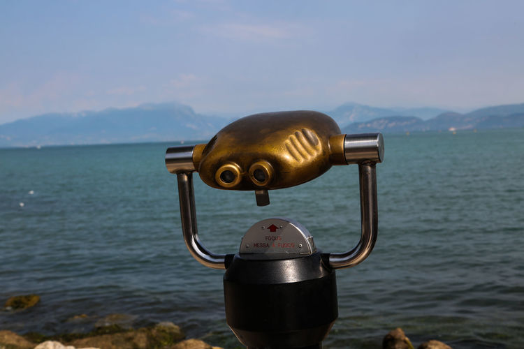 Lake Garda Beauty In Nature Binoculars Close-up Coin Operated Coin-operated Binoculars Day Focus On Foreground Hand-held Telescope Metal Mountain Nature No People Outdoors Scenics - Nature Sea Security Sky Tranquil Scene Tranquility Water