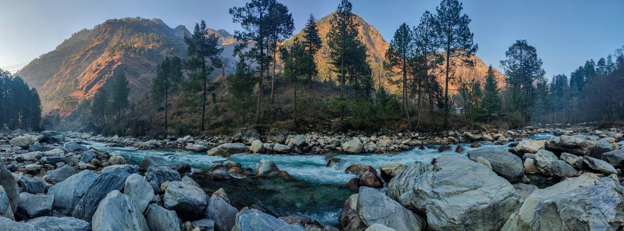 Panoramic view of rocks, trees and river against sky