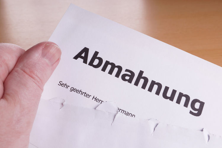 Abmahnung = German cease-and-desist letter Abgemahnt Abmahnung Abmahnwelle Brief Business Cease-and-desist Envelope Hand Holding Law Legal Letter Office Open Warning