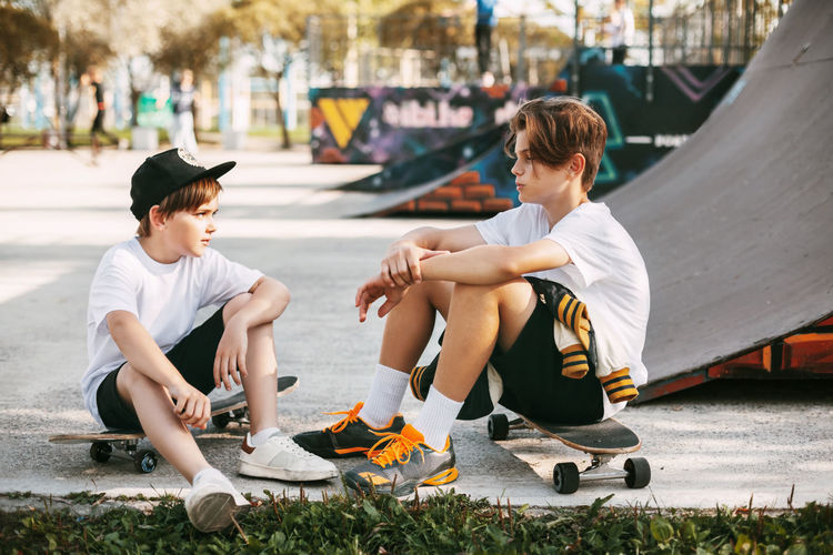 Two best friends in a skateboard park. friends sit on skates in the park, talking and smiling.