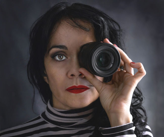 Brunette woman with camera lens in her eye Portrait Headshot One Person Holding Camera - Photographic Equipment Photography Themes Looking At Camera Indoors  Studio Shot Photographing Young Adult Front View Technology Adult Gray Background Activity Lens - Optical Instrument Looking Through An Object Young Women Body Part Photographer Digital Camera Hairstyle Human Face