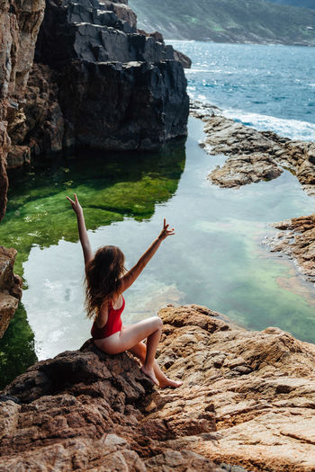 Rock Water Rock - Object Solid One Person Leisure Activity Full Length Lifestyles Real People Beauty In Nature Nature Sitting Rock Formation Young Adult Women Adult Day Clothing Human Arm Arms Raised Hairstyle Outdoors