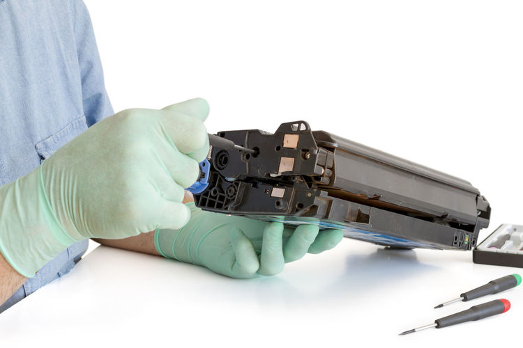Cropped Image Of Person Repairing Machinery At Table Against White Background
