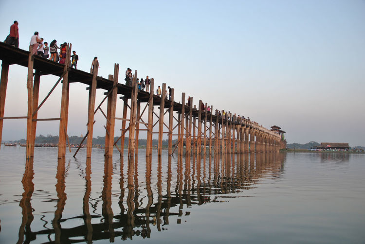 Tourists walking on pier over lake