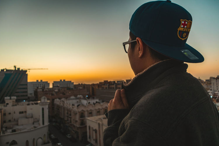 Rear view of man looking at cityscape
