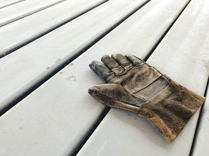 The welder leather glove on steel bar Aged Old Leather Glove Hard Working Man! Tuff Job Composition Art Perspective View High Angle View Close-up Pattern No People Indoors  Shoe Day Nature Full Frame White Color Table Still Life Body Part Shiny Metal