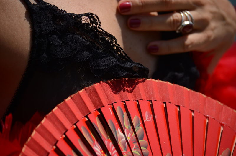 Close-up midsection of woman holding hand fan
