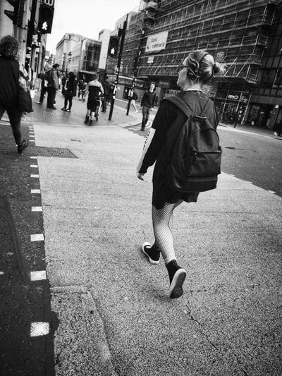 Rear view of women walking on sidewalk in city