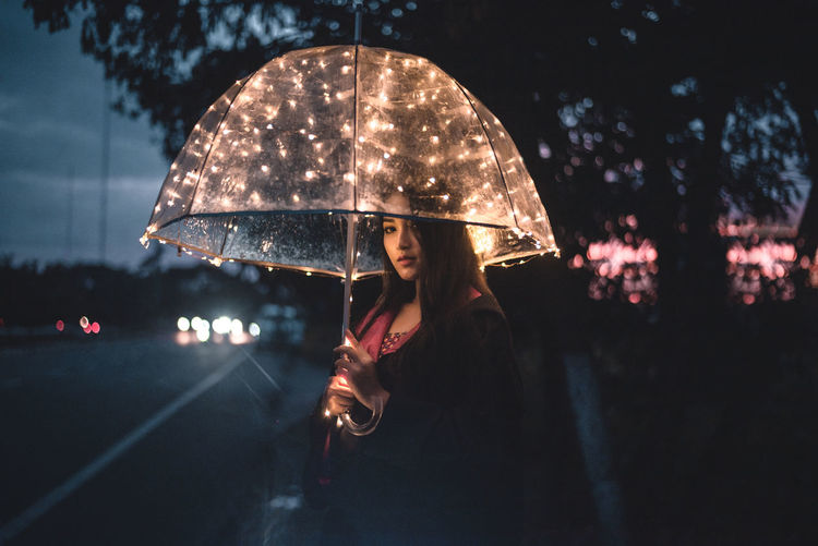 Woman standing with umbrella in rain