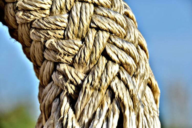Close-up of rope tied to wooden post against sky