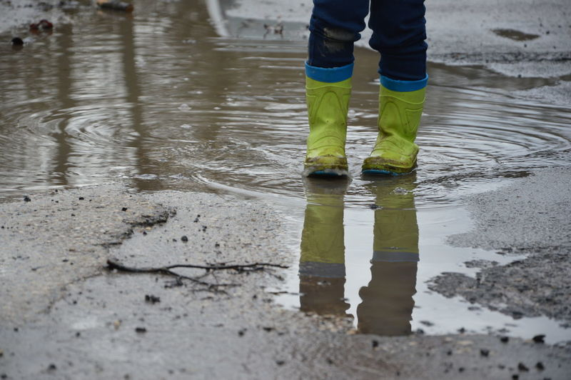 Low section of person wearing boots while standing in puddle