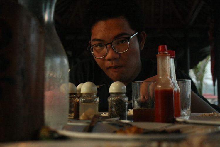 Portrait of teenage boy sitting at restaurant table