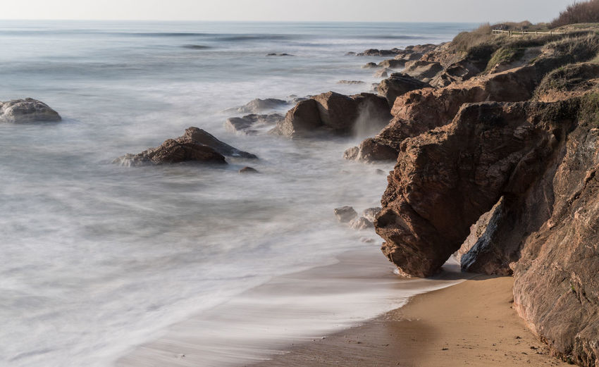 Scenic view of rocky beach against sky in long exposure