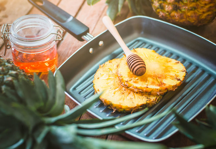 Close-up of honey dipper and pineapple slices in cooking pan