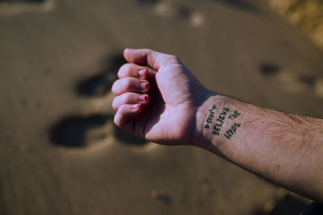 Cropped hand of man with tattoo at sandy beach