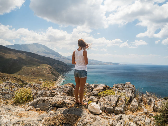 Travel Beauty In Nature Full Length Lifestyles Looking At View Mountain Nature Non-urban Scene One Person Outdoors Real People Rock Scenics - Nature Sea Sky Standing Water